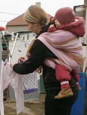věšení prádla s dítětem v šátku