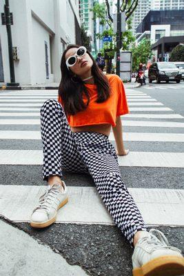 oranžový crop top a šachovnicové čiernobiele nohavice
