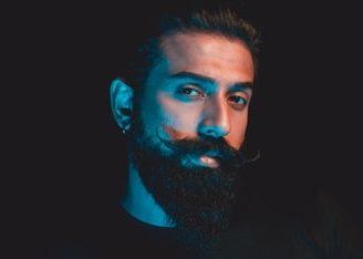muž s tvarovanými fúzami a zarovnanou hustou bradou
