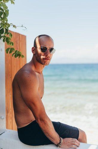 holohlavý muž v plavkách a v okuliaroch slnečných na pláži