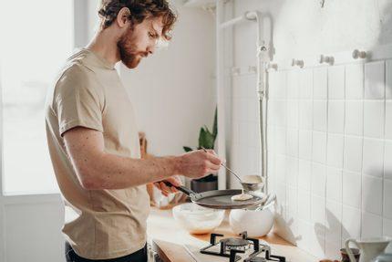 muž v kuchyni pripravuje lievance
