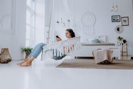 žena počúva hudbu so slúchadlami na ušiach v závesnom bielom kresle