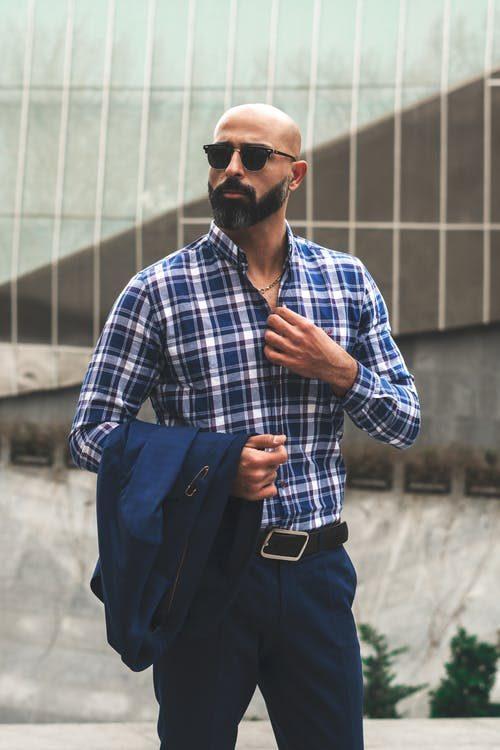 holohlavý muž s bradou a slnečnými okuliarmi v kockovanej košeli