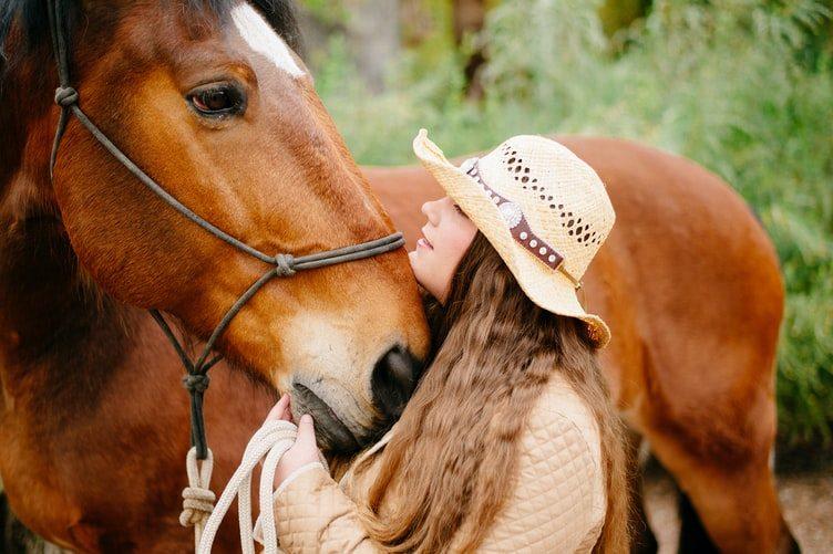 hnedý kôň a žena v klobúku, čo ho hladká