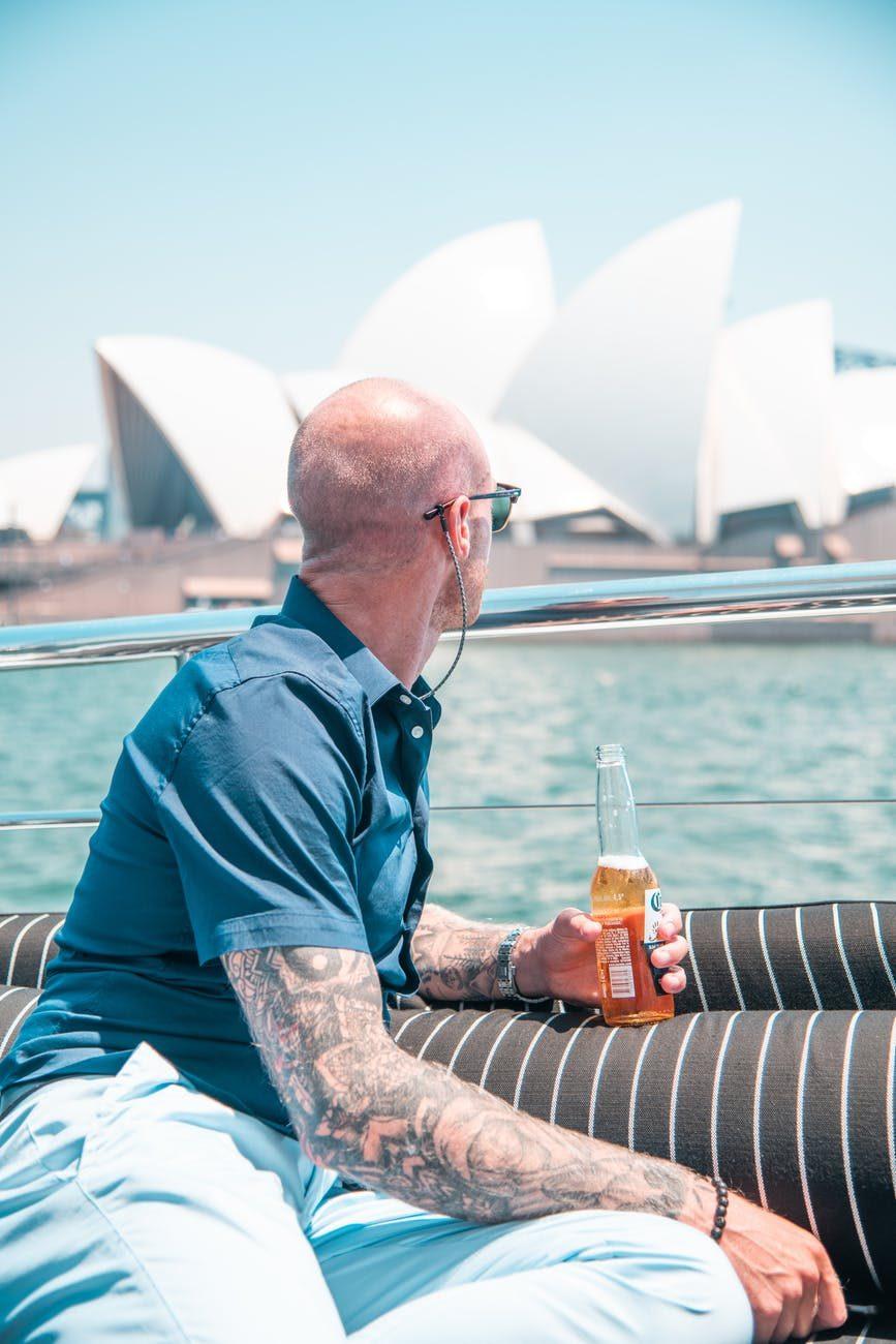 plešatý muž pije drink na lodi