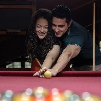 muž a žena flirtují při hraní kulečníku