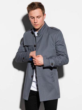 Muž v šedém jarním kabátu, trenčkotu, s černými kalhotami