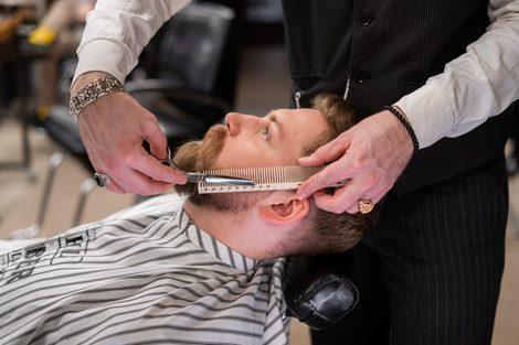 muži u holiče stříhají / upravují bradu