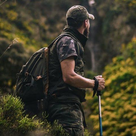 turistika v horách - muž v kšiltovce, batohem a turistickými paličkami