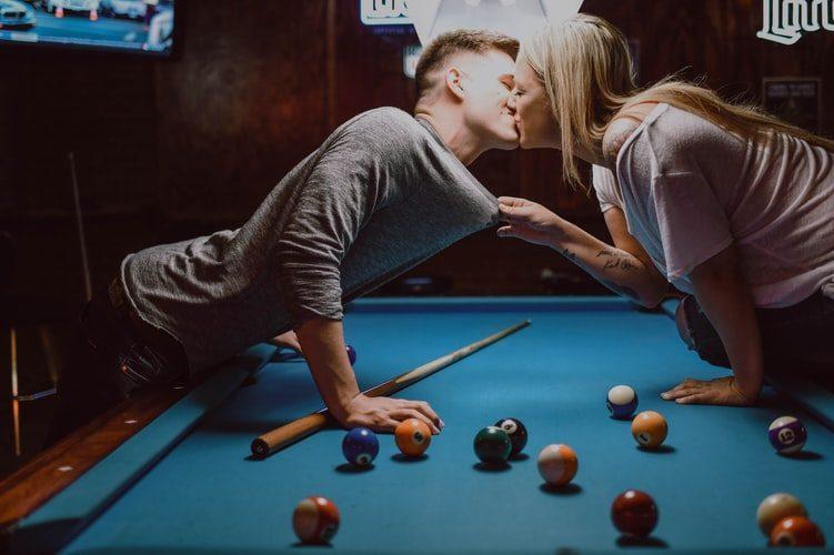 muž a žena flirtují, líbají se nad kulečníkovým stolem